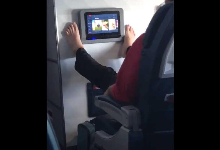 Video Man Using feet for TV touchscreen on plane