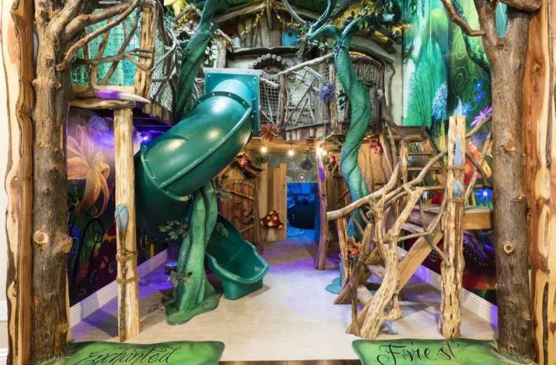 A fantasy forest playroom has climbing frames, slides and hidden doors