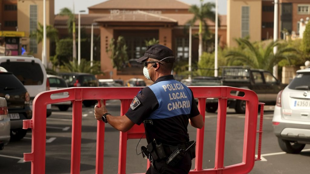 A Spanish police officer sets a barrier blocking access to the H10 Costa Adeje Palace hotel in Tenerife. (AP Photo)