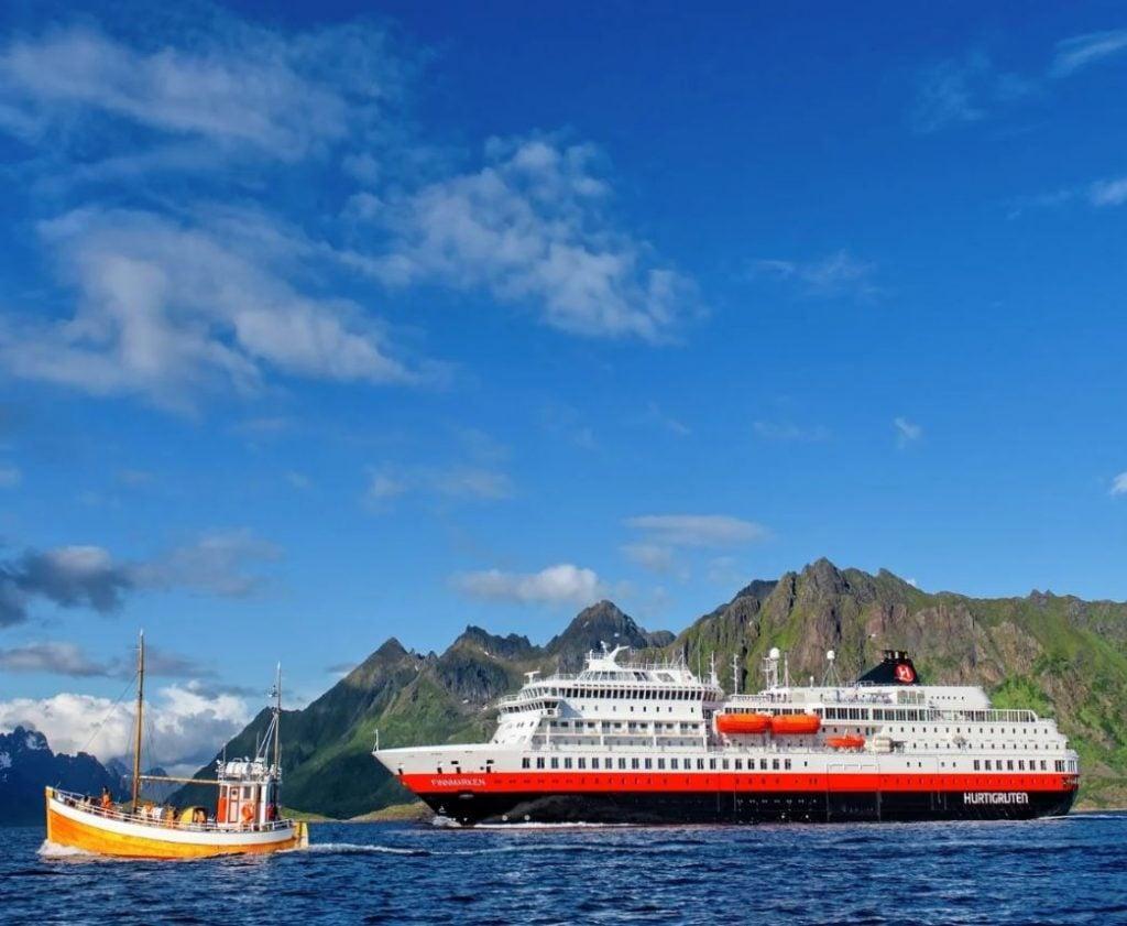 Hurtigruten Cruises ship beside small boat in norway
