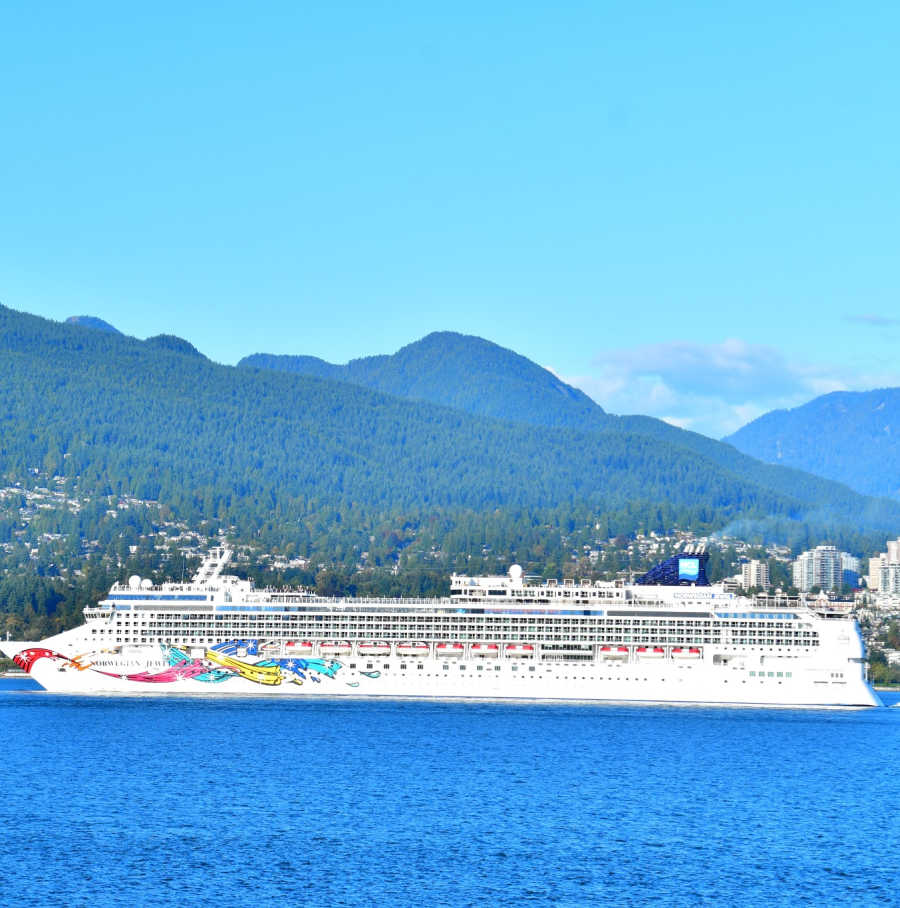 Norwegian cruise ship with moiuntains in background