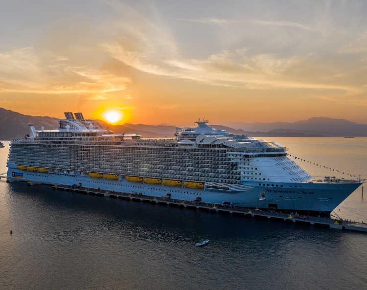 Royal caribbean cruise ship docked as sunsets behind it