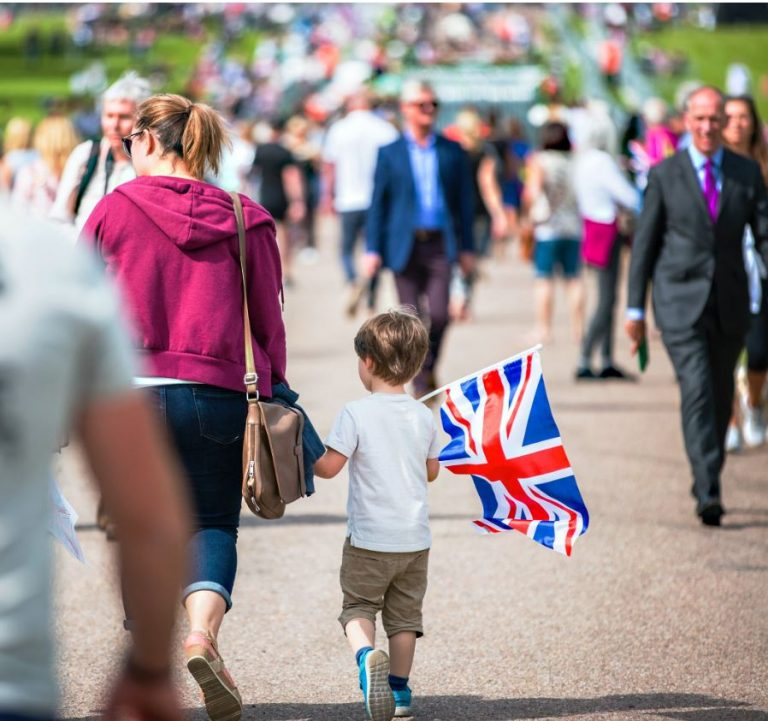 Woman and son tourists carrying british flag