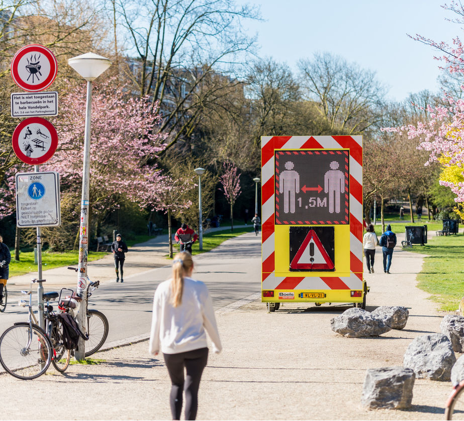 Keep Distance of 1.5 meter Warning Sign on Digital Display in a public park. Amsterdam, Netherlands
