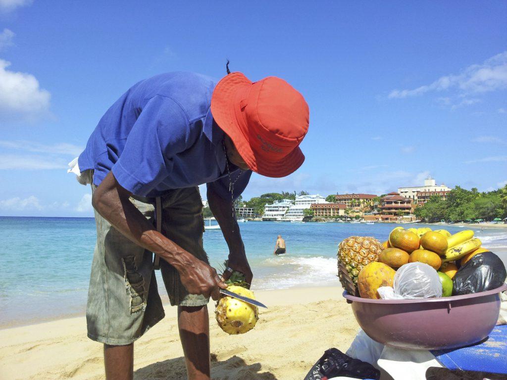 man sells ananas at the beach