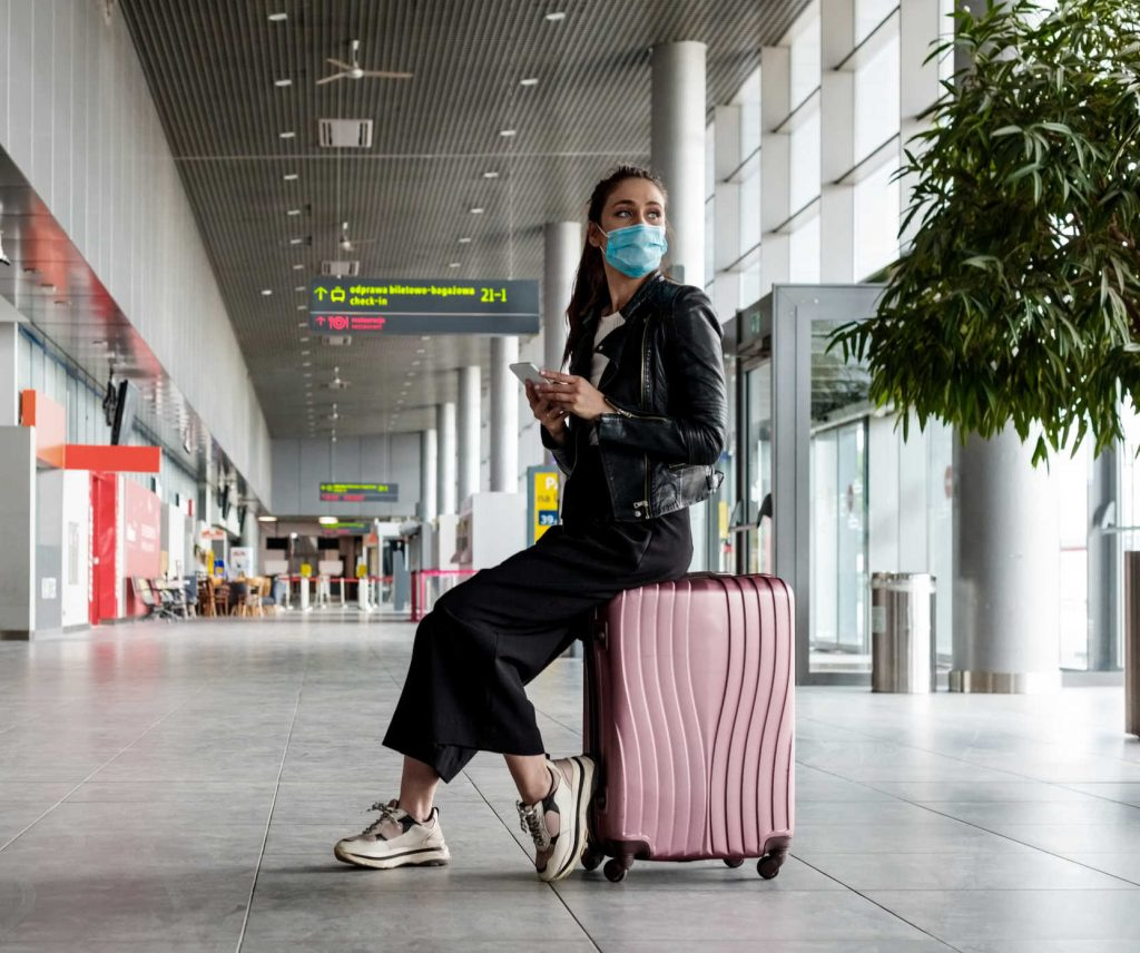 Woman checking COVID-19 entry requirements of a country at the airport