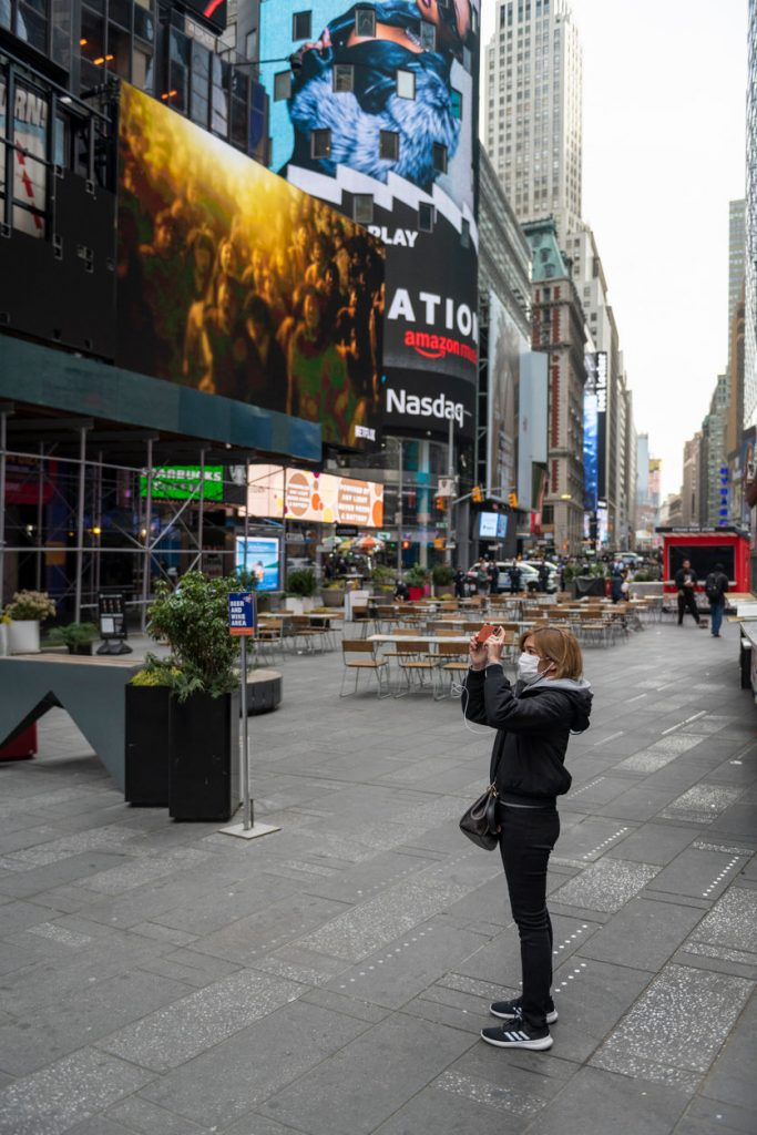 Tourist wearing a mask takes a picture in Times Square during COVID-19
