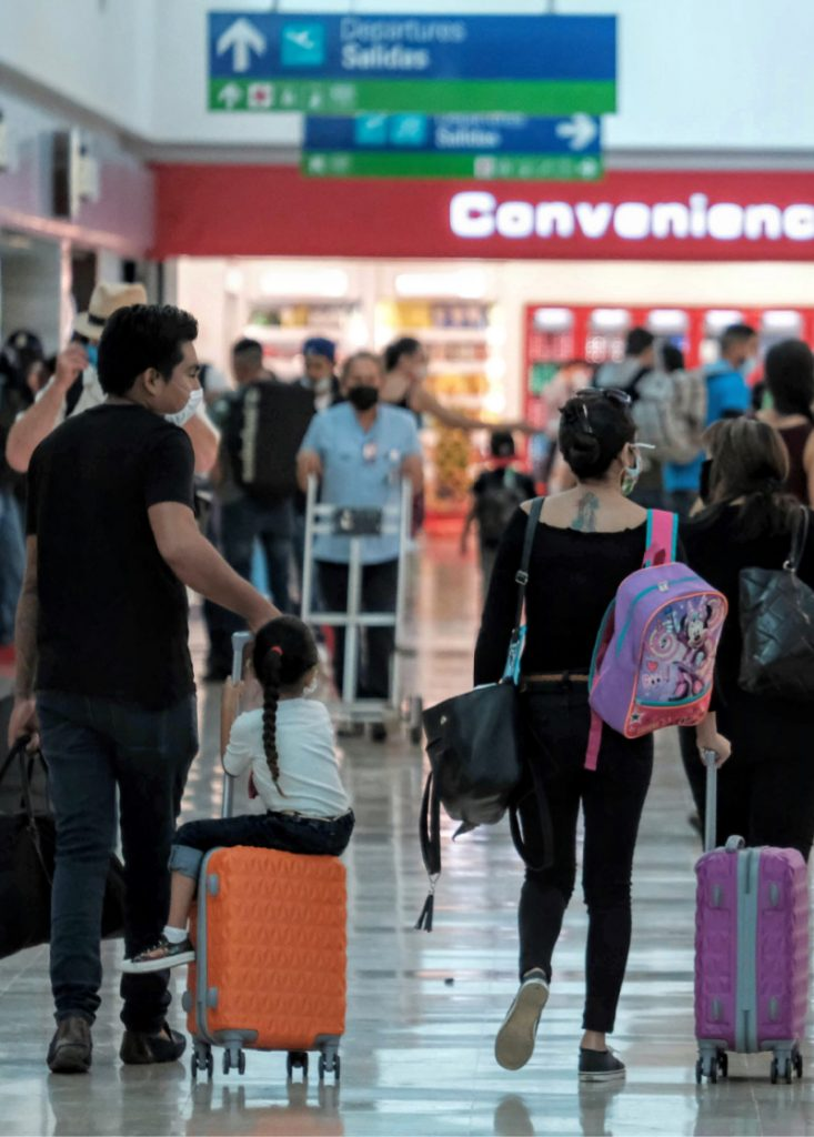 Travelers arrive at the international airport in Cancun wearing masks