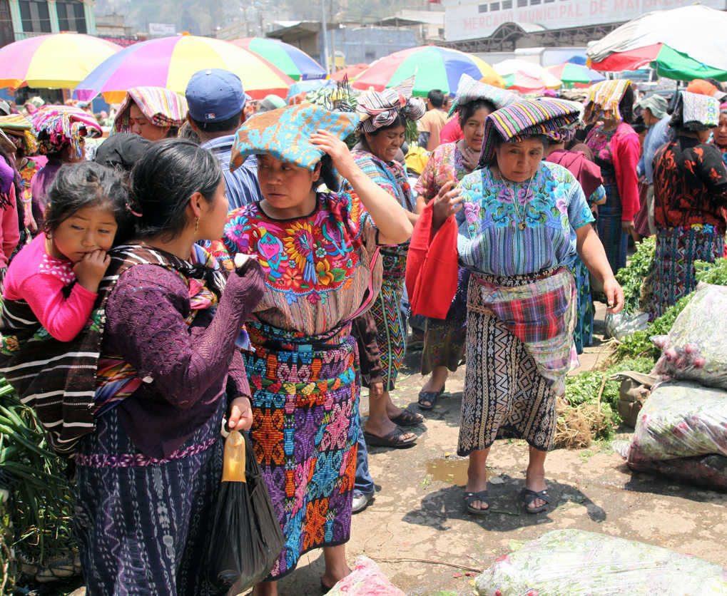 Woman prepares to sell radishes at market day in the center of Zunil, Guatemala