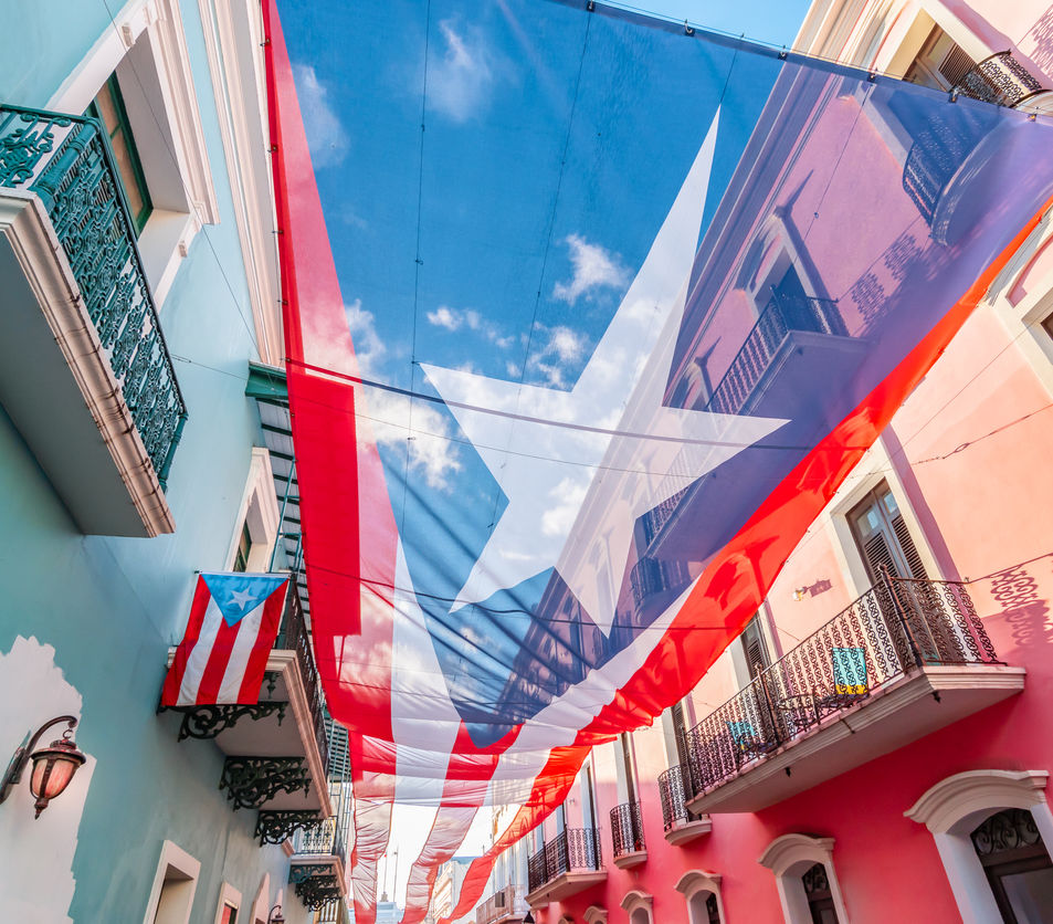 city centre of San Juan with large Puerto Rican flag above the street