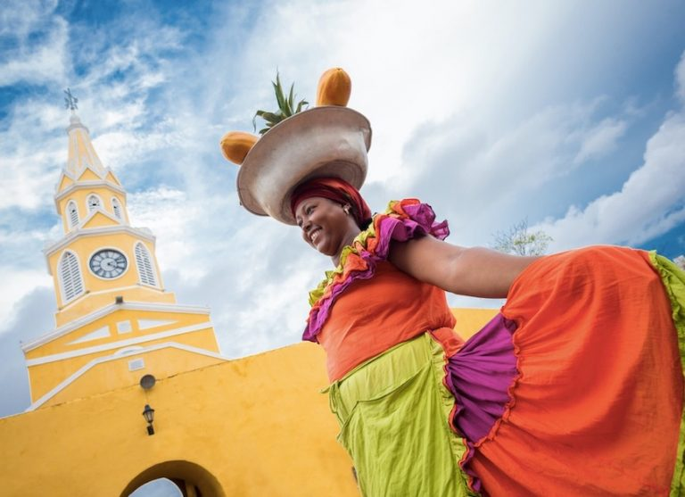 Happy Palenquera selling fruits in Cartagena
