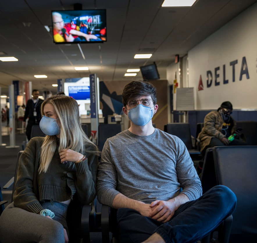 Travelers wait at LaGuardia airport to board a flight to Cancun