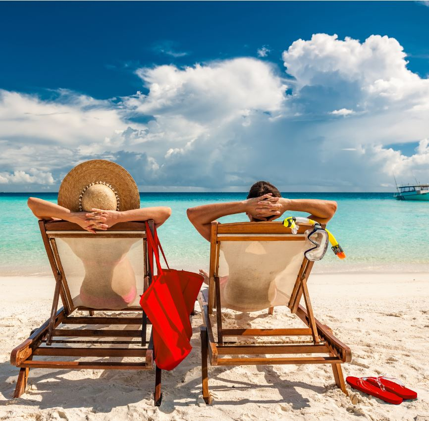 Couple on beach loungers in Caribbean