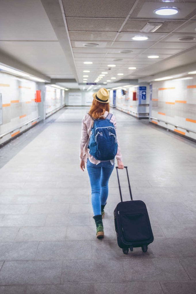 American traveler at airport with suitcase
