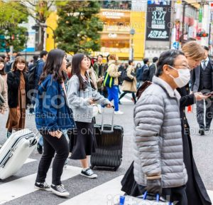 tokyo travelers with luggage in masks