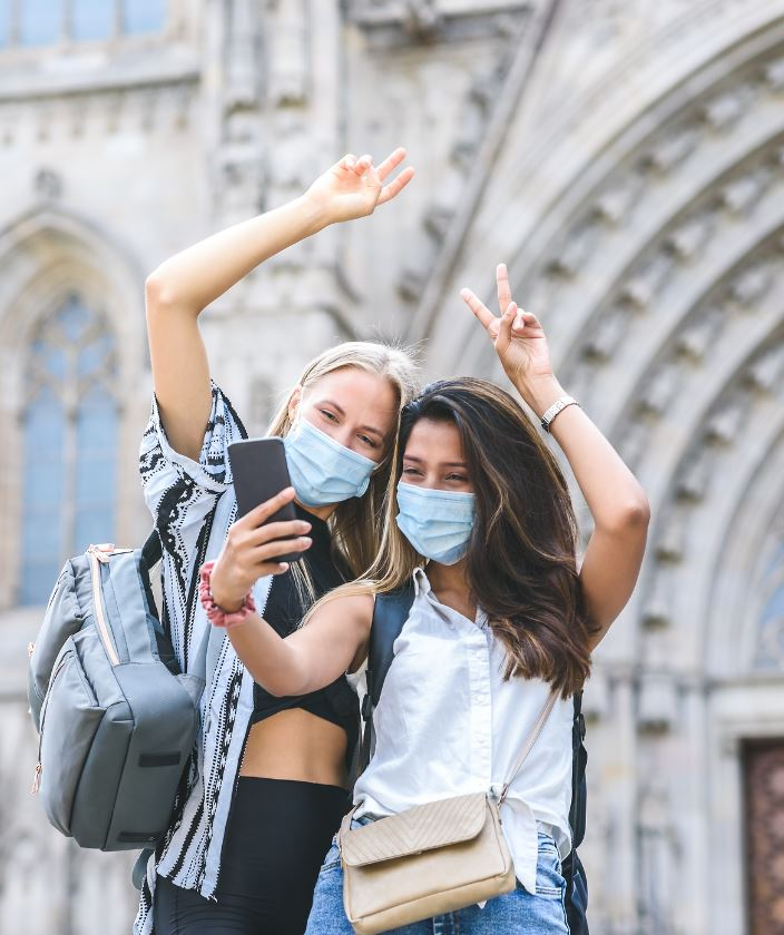 Tourists women masks travel selfie at a cathedral