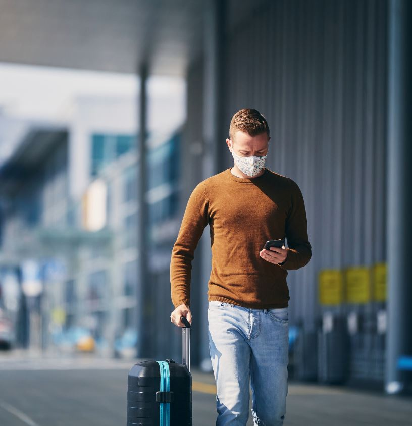 man holding his phone and carrying a wheelie suitcase arriving at the airport outside