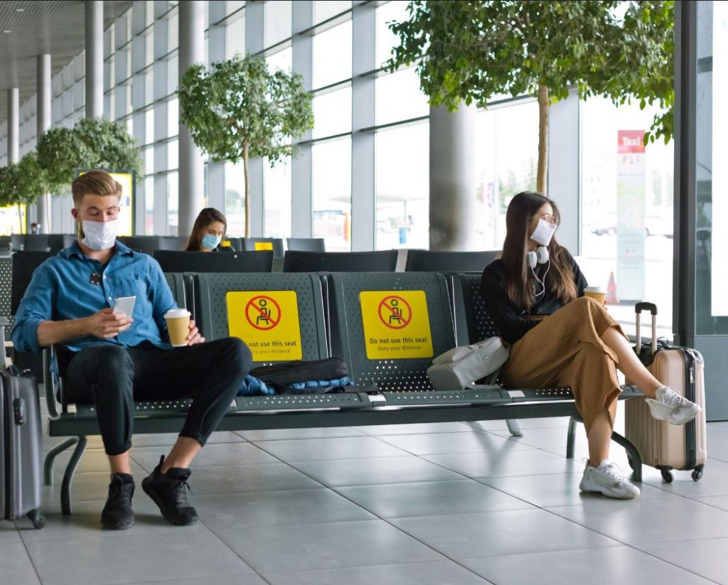 Travelers wearing masks social distancing