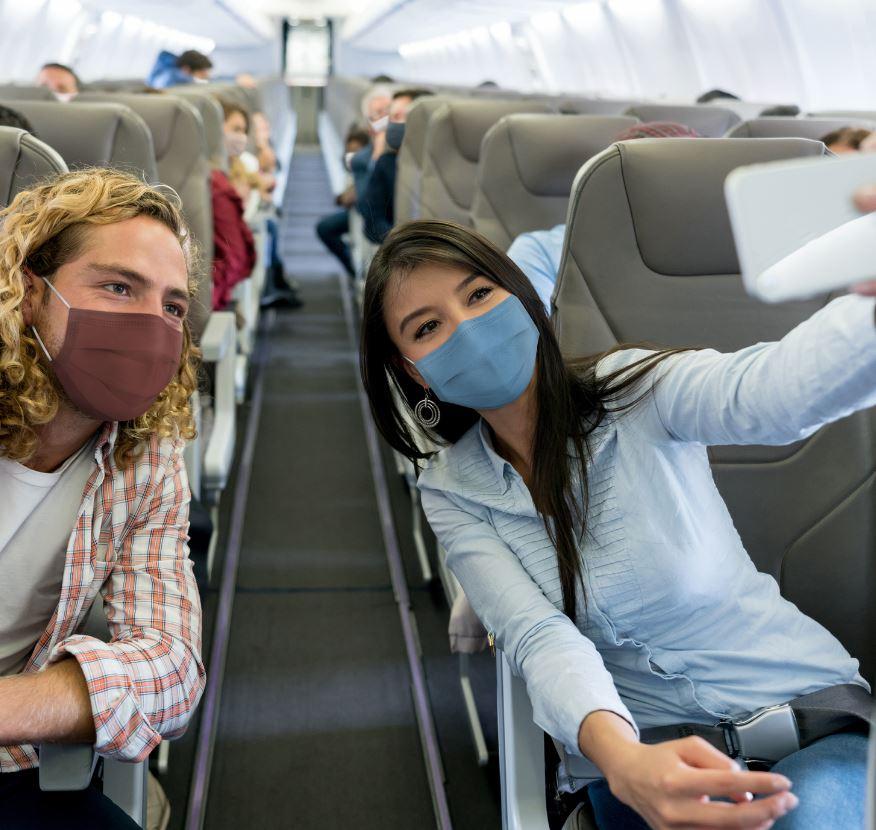couple mask airplane selfie