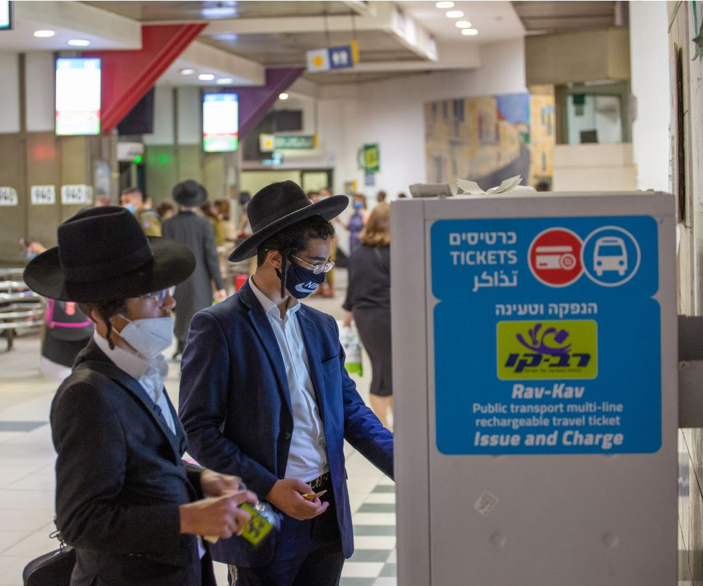 israeli travelers buying tickets wearing masks