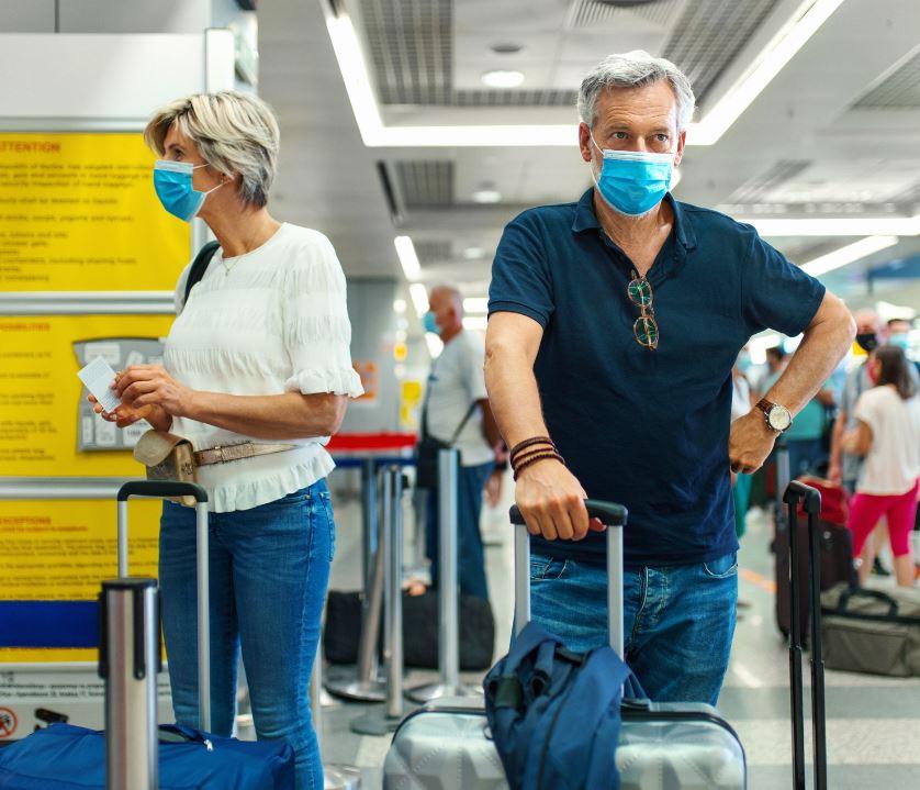 masked travelers waiting at airport