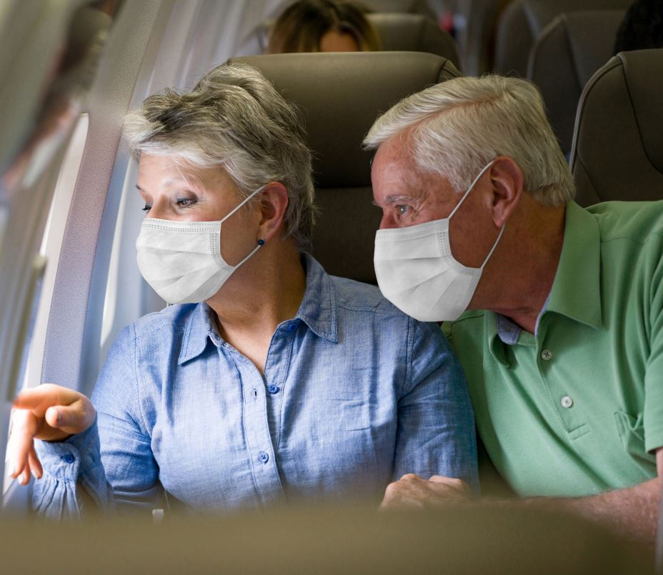 older couple wearing masks on plane
