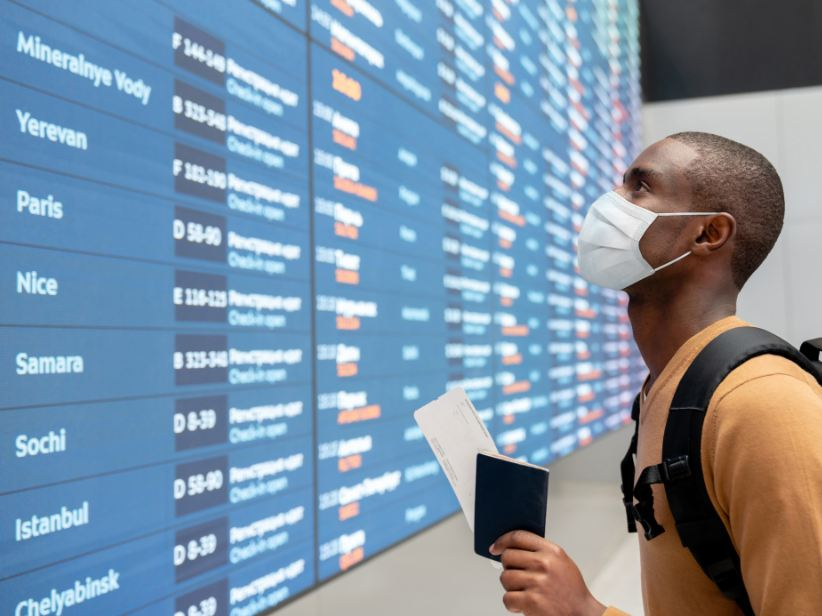 traveler in mask looking at flights