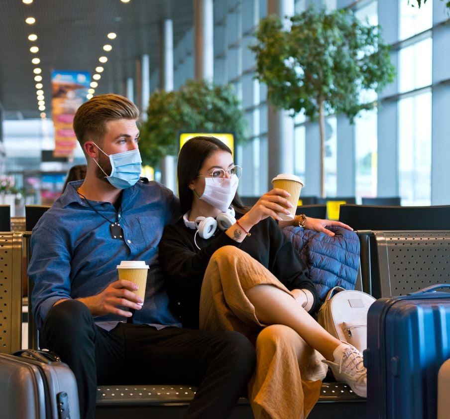 uk couple wearing masks at airport