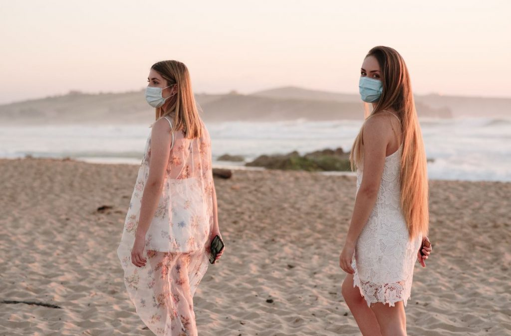 tourists wearing face masks on beach