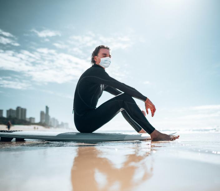 man sitting on surf board in australia wearing mask