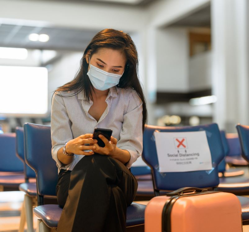 masked woman checking phone at airport