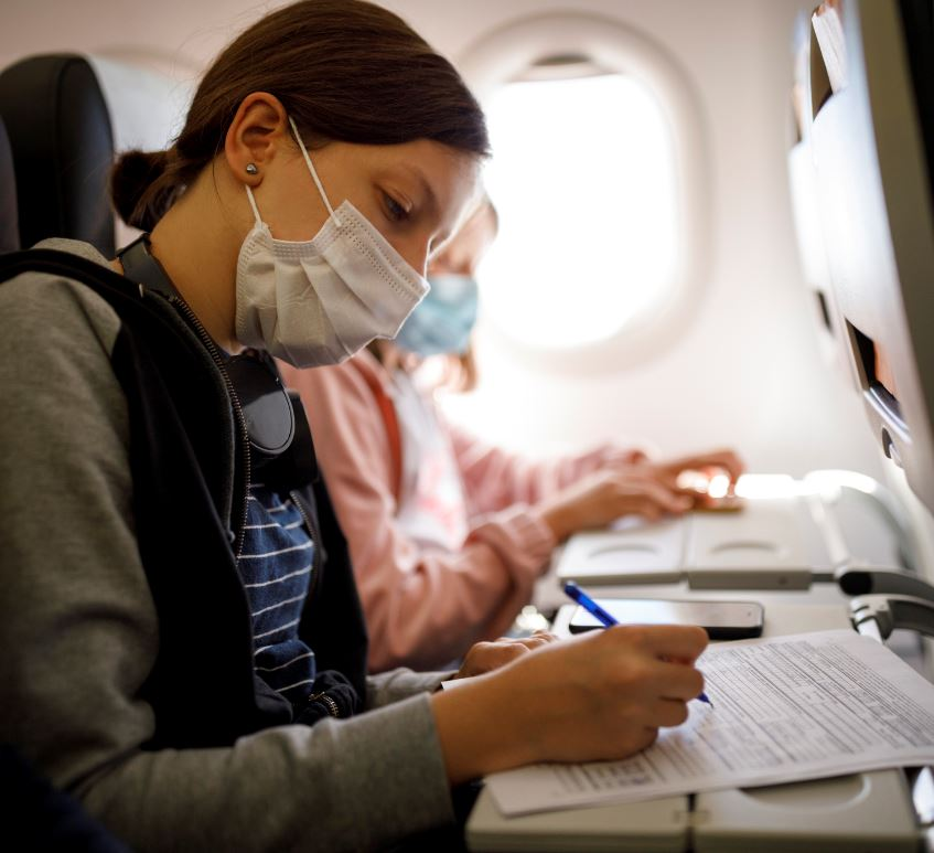 masked woman on plane filling out form