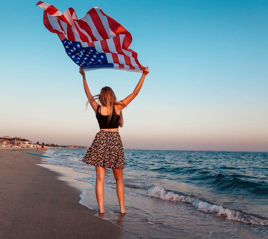 woman holding american flag on beach
