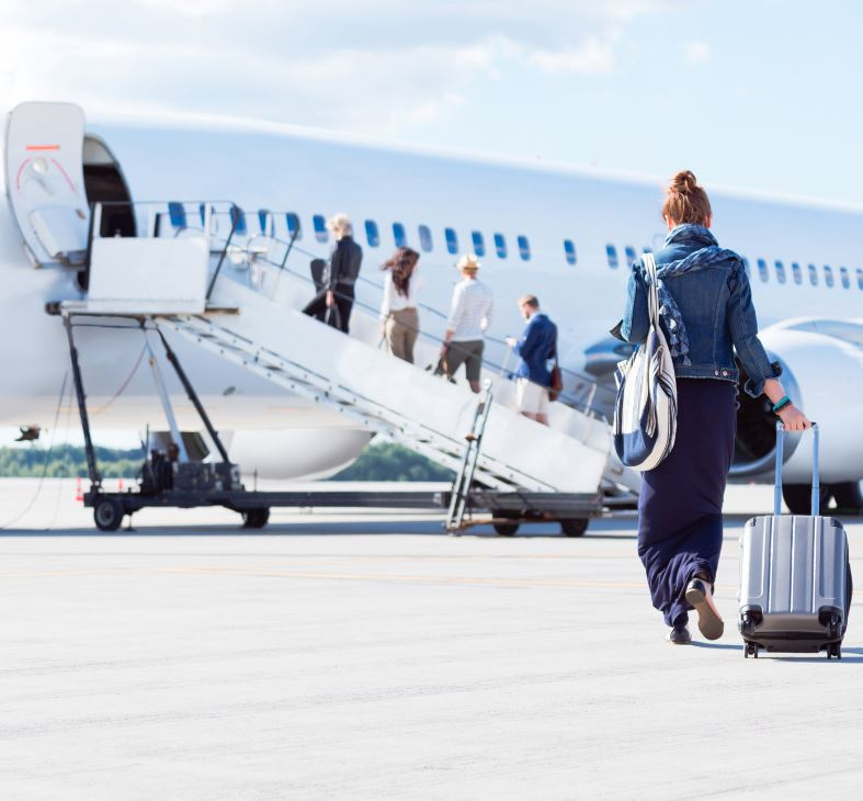 woman wheeling small suitcase to board plane
