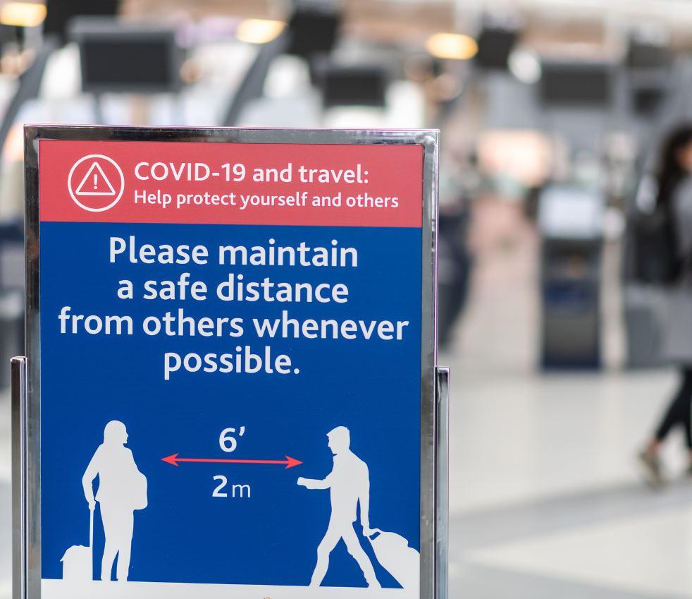 covid warning sign at airport