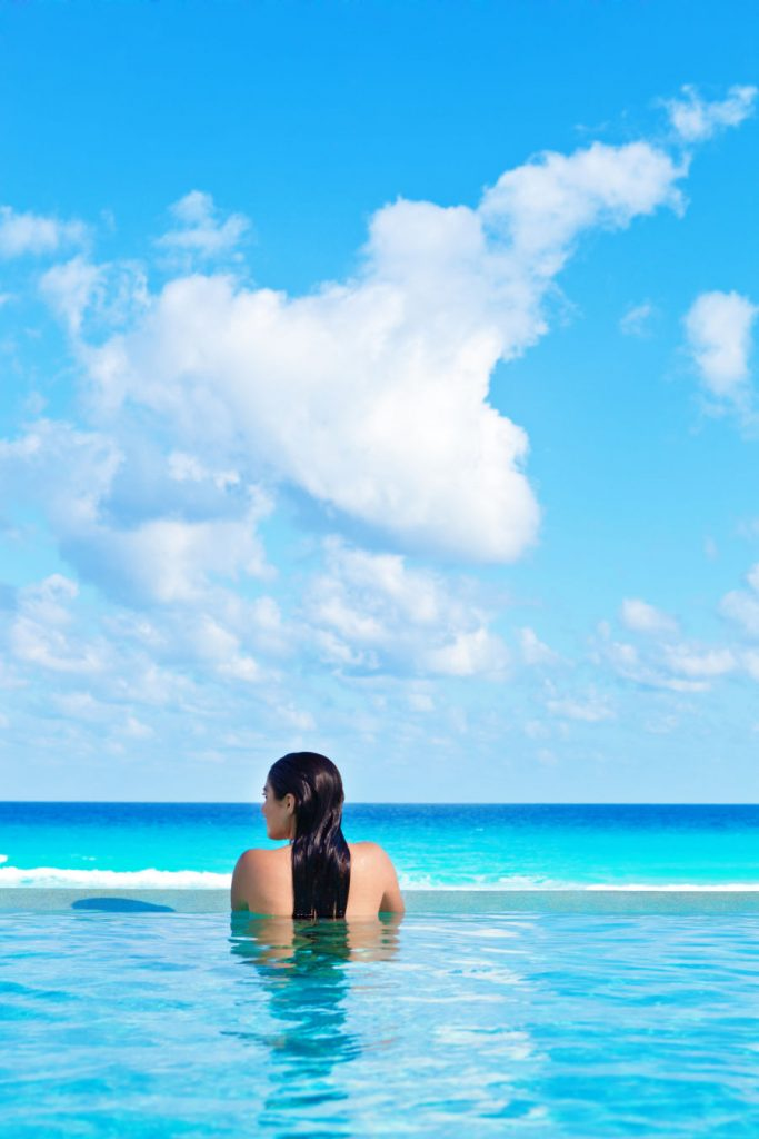 Woman in Pool overlooking ocean in Cancun, Mexico (1)