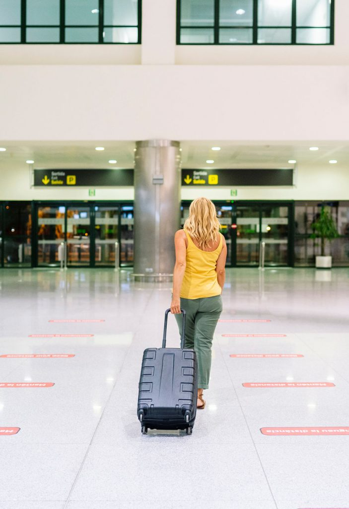 female american traveler with luggage at airport