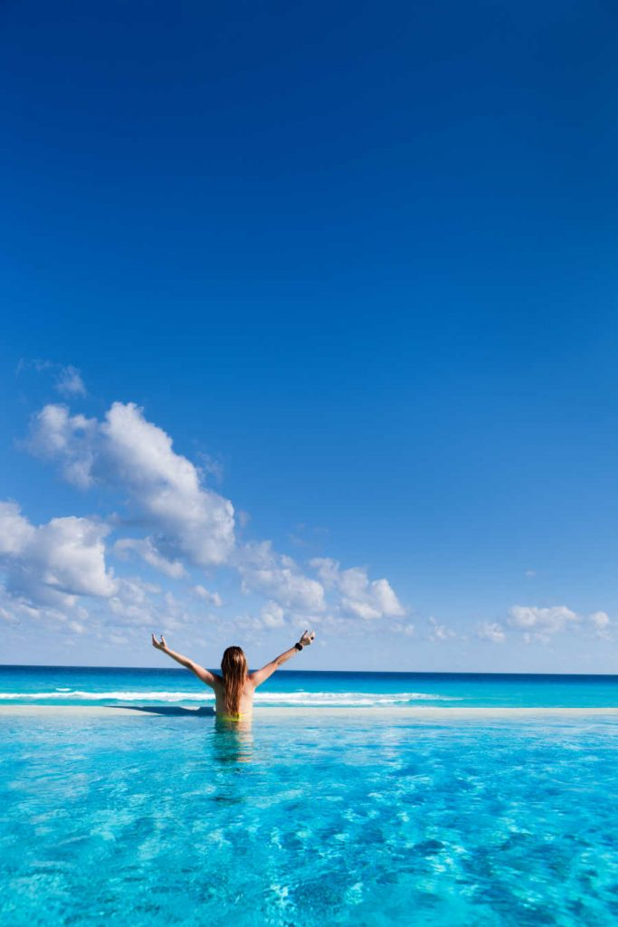 ocean front pool traveler with arms up in cancun