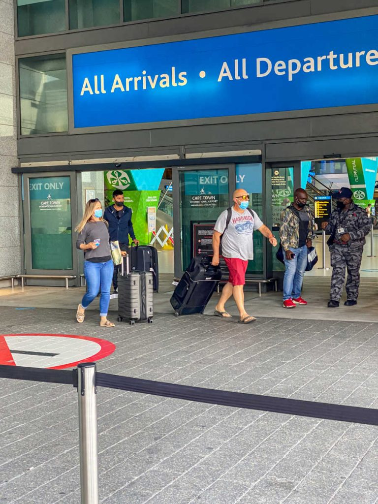 passengers departing airport arrivals wearing masks
