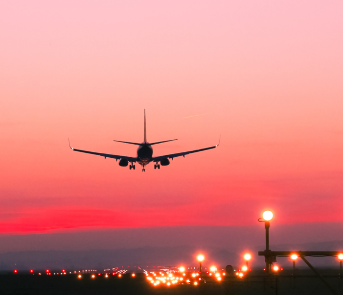 plane landing runway sunset