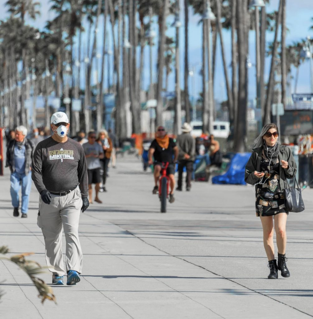 tourists walking down Venice beach face masks California