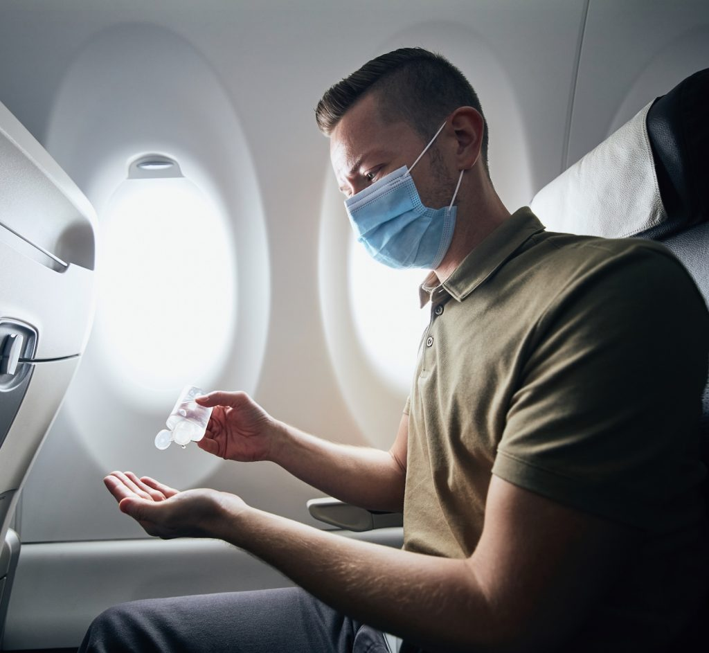 traveler sanitizing on flight during pandemic