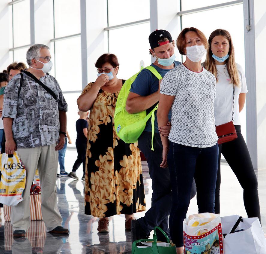 travelers at airoprt wearing masks boarding flight