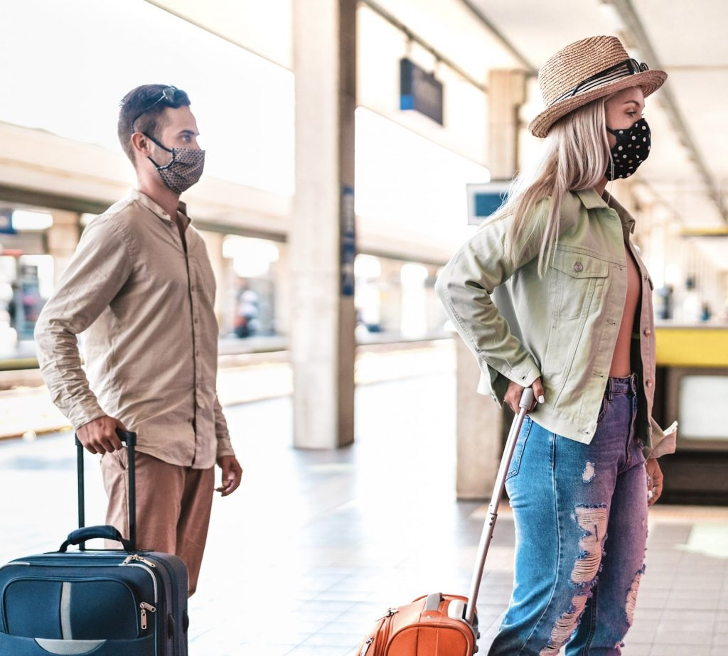 travelers with face masks social distancing suitcases