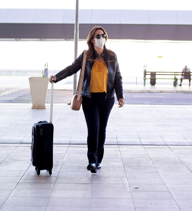 woman arrives at airport wearing mask