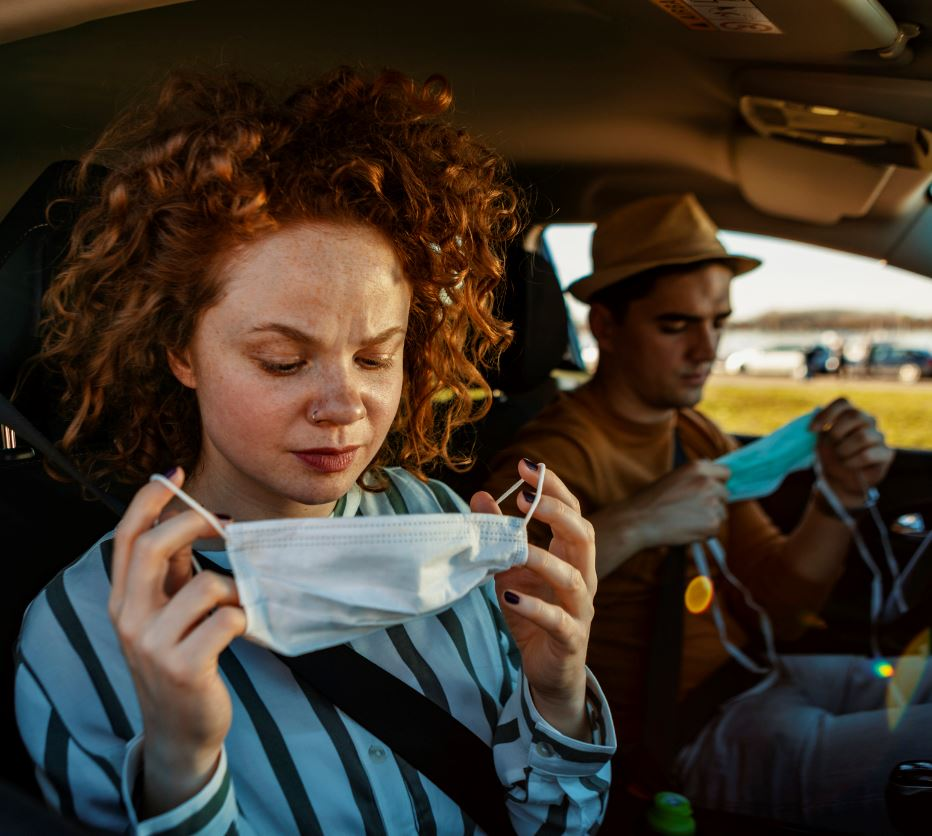 Couple putting on masks in car
