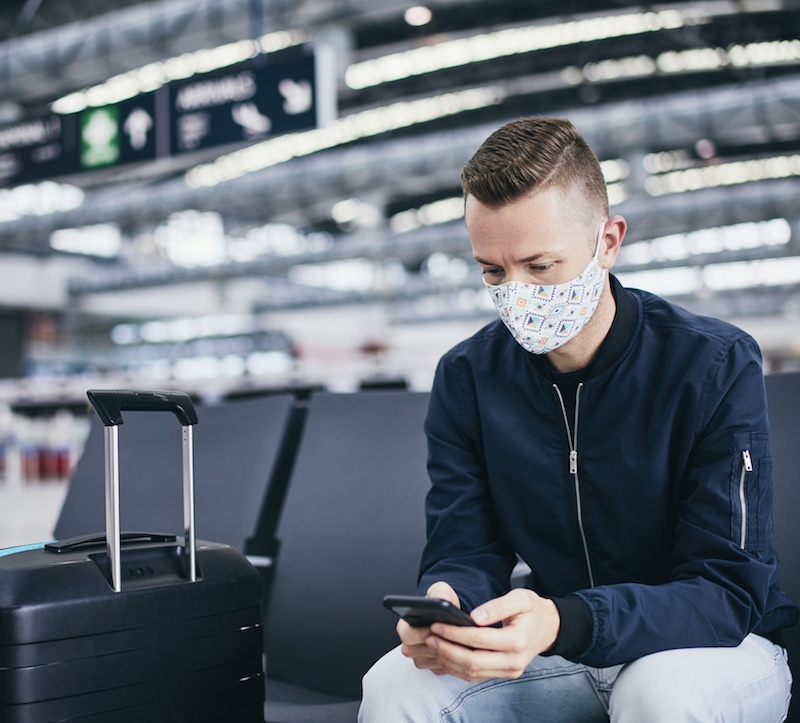 Man wearing face mask on phone waiting for flight at airport