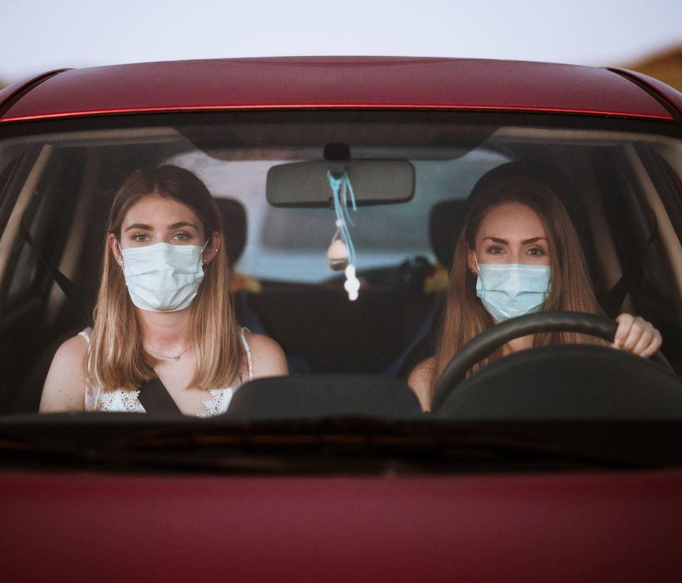 two women in car wearing in masks