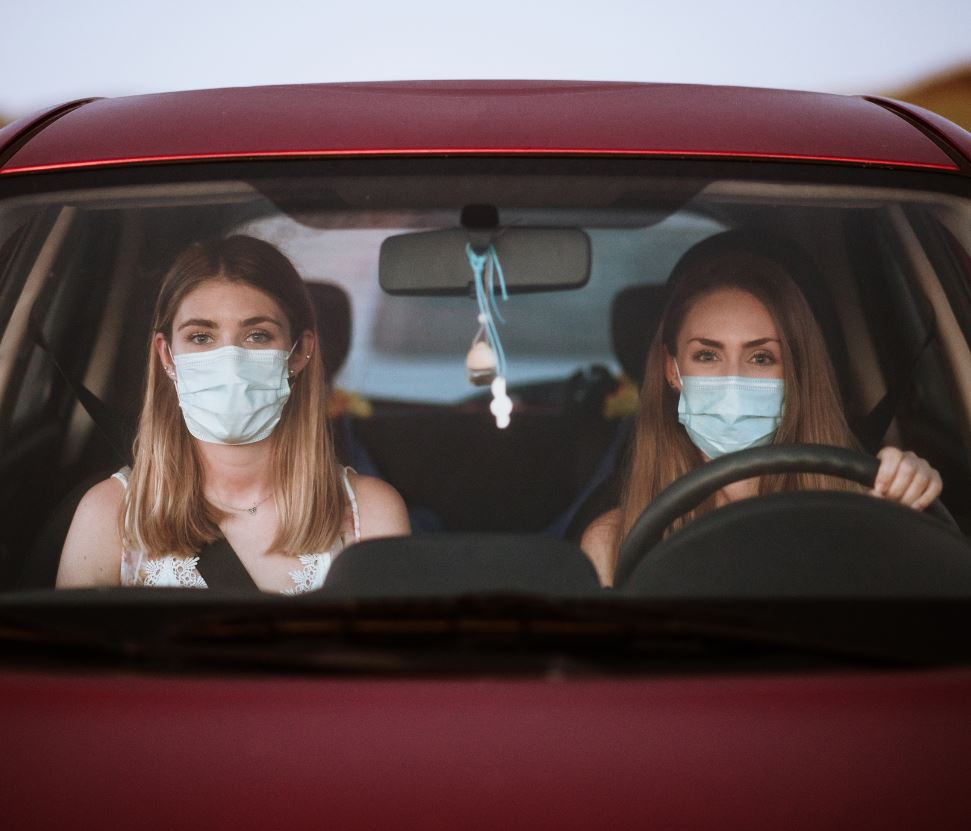 women in masks driving