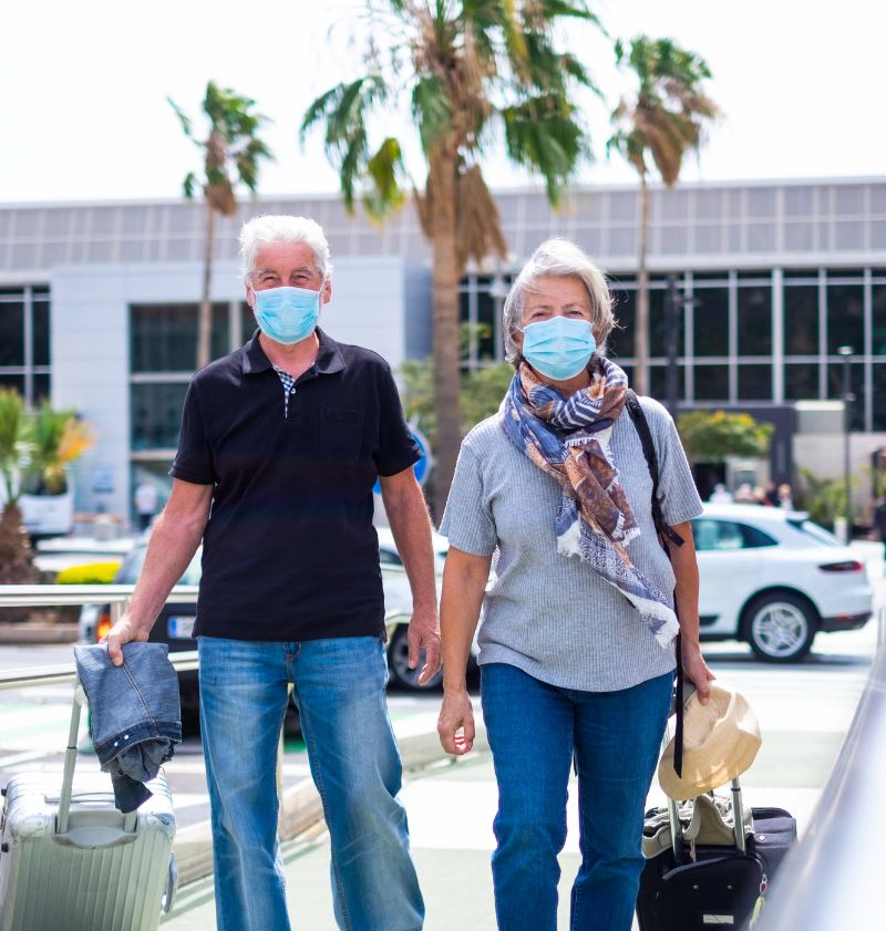 Senior couple with luggage and mask at airport
